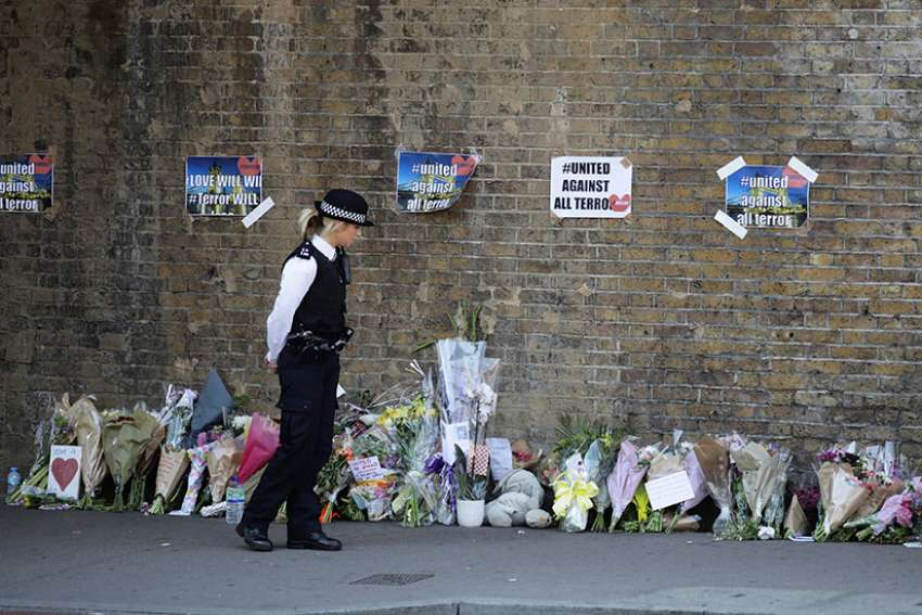A police officer stands in front of messages and tributes June 19 left near where a man died and 10 people were injured after a van was rammed into a crowd of worshippers near a mosque in north London. A 48-year-old man was arrested in the collision with pedestrians outside the Muslim Welfare House, police said.