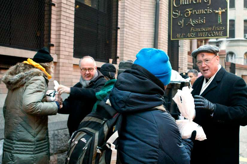 Cardinal Timothy M. Dolan of New York hands out sandwiches at the St. Francis of Assisi Church Breadline in New York following a Feb. 18 Ash Wednesday Mass.