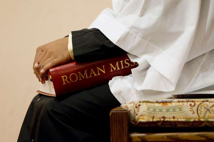 An altar server holds a copy of a Roman Missal during Mass at St. Joseph Catholic Church in Alexandria, Va., in this 2011 file photo.