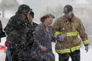 A woman is evacuated from a building where a shooter was suspected to be still holed up at a Planned Parenthood clinic Nov. 27 in Colorado Springs, Colo. Police say Robert Lewis Dear killed three people during the shooting rampage and hours-long standoff at the clinic and was later taken into custody.