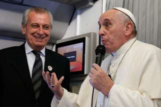 Pope Francis refers to Alberto Gasparri, left, papal trip planner, while answering a question from a French journalist aboard his flight to Manila, Philippines, Jan. 15.