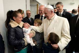 Pope Francis blesses a baby during a visit to a Caritas center for the homeless near the Termini rail station in Rome Dec. 18. The pope opened a Door of Mercy at the center.