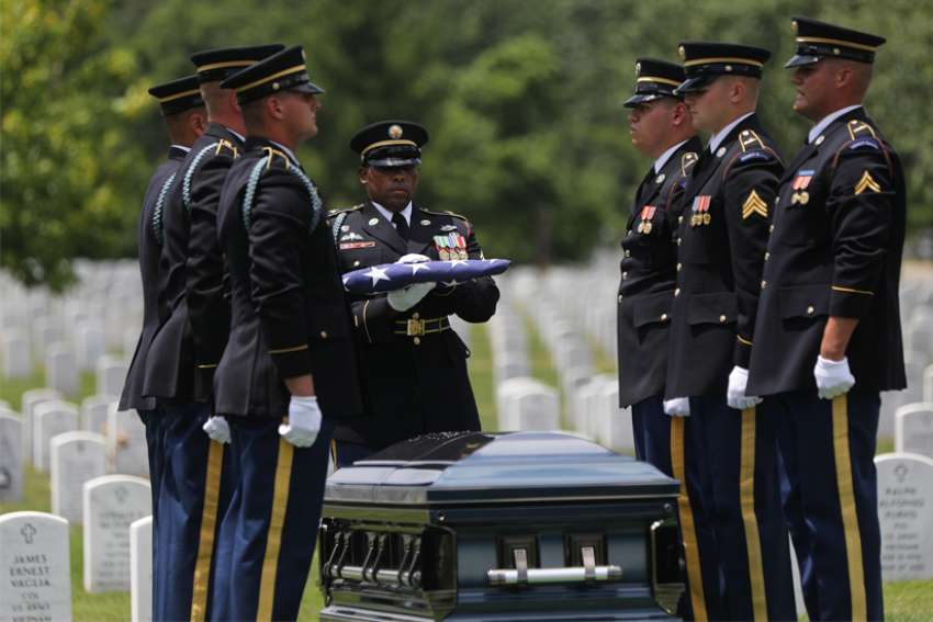 An officer with the U.S. Army military honor guard holds the U.S. flag over the casket of the late Carl Mann Sr., a World War II veteran, during his burial June 6, 2019, at Arlington National Cemetery in Virginia, outside Washington. In a joint appeal marking 80 years since start of World War II, Polish and German bishops warn that Europeans still need to work toward peace and unity.