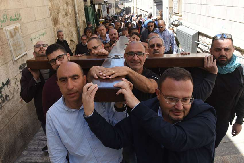 "Men carry a large wooden cross during a procession on the Via Dolorosa, ""The Way of Sorrow,"" the path believed to be taken by Jesus Christ to his crucifixion on Calvary, on Good Friday April 14, 2017, in Jerusalem's Old City."