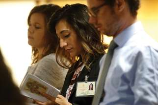 Yadira Vieyra, center, a synod delegate who works with migrant families in Chicago, attends a session of the Synod of Bishops on young people, the faith and vocational discernment at the Vatican Oct. 11.