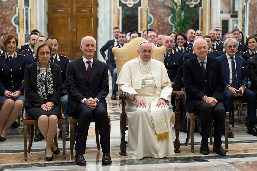 Pope Francis poses March 26 in Clementine Hall at the Vatican with Italian state police who work in the General Inspectorate for Public Security. The pope thanked the officers for their service and praised their personal sacrifice in protecting others.