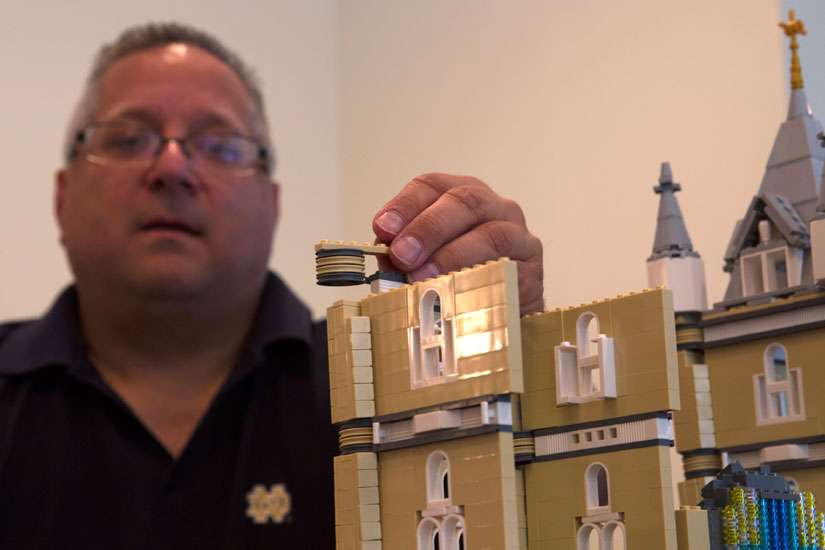 Fr. Bob Simon, pastor of St. Catherine of Siena parish in Moscow, Pa., places a Lego piece on a model church he is building in a spare room in his rectory Oct. 24. Simon says his Lego-building hobby has served as an evangelization tool.