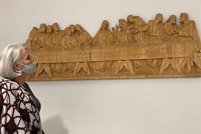 Connie Leon looks over The Last Supper wood relief carving she donated to St. Joseph's Morrow Park Catholic Secondary School.