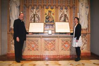 Msgr. Murray Kroetsch, chancellor of the Diocese of Hamilton, with library and archives director Dominy Williams and the historic papal bulls declaring Hamilton a diocese.