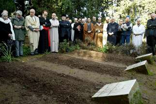 Cardinal Philippe Barbarin of Lyon, France, fourth from left, prays in 2007 in Medea, Algeria, during an interfaith service at the graves of the seven Trappist monks who were killed in 1996.