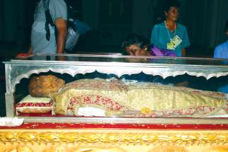 Pilgrims pray by and view the body of St. Francis Xavier during an exposition of the saint in December 2004 at the Se Cathedral in Goa, India.