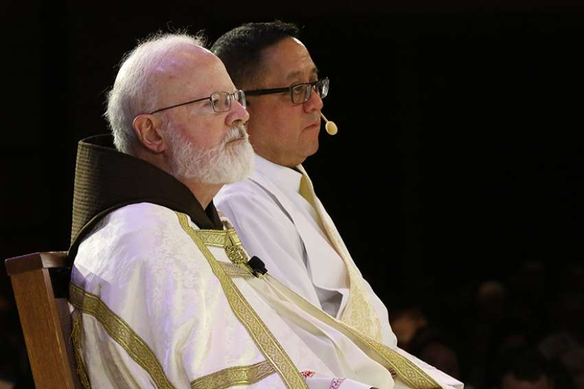 "Boston Cardinal Sean P. O'Malley and Deacon Bernie Nojadera, executive director of the U.S. bishops' Secretariat for Child and Youth Protection, are pictured during the 2017 Catholic convocation in Orlando, Fla. In an Aug. 13 interview, Deacon Nojadera said he and his staff at the secretariat are receiving calls from people concerned about the current abuse crisis in the church. ""Our fist job,"" he said, ""is to listen, to be empathetic."""
