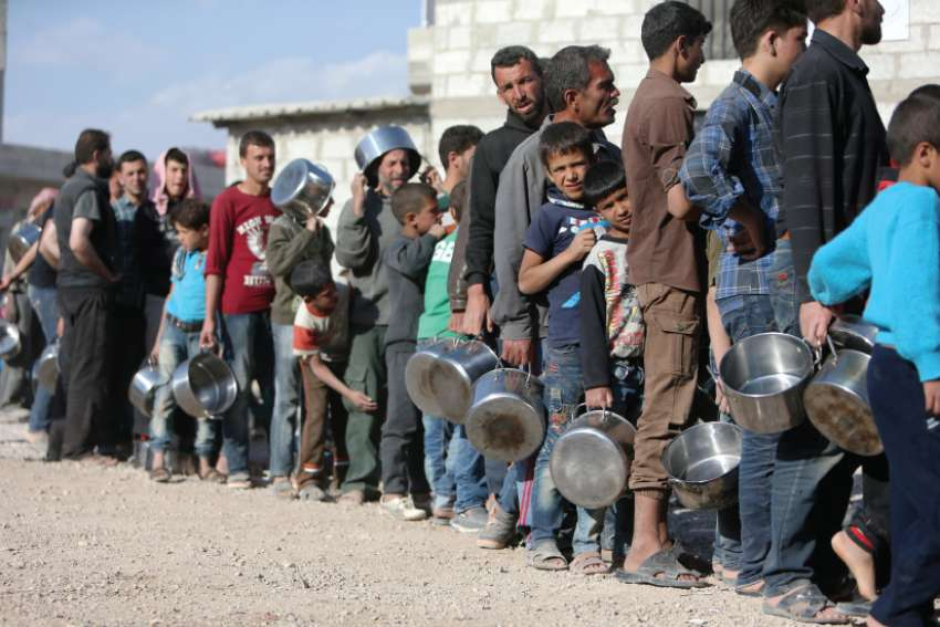 Internally displaced Syrians wait in line for food April 15 at a camp outside Damascus. The United States, France and Britain launched airstrikes in Syria to punish President Bashar Assad for an apparent chemical attack.