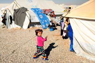 A displaced Iraqi child walks outside tents Dec. 9 at the Hassan Sham camp near Mosul.