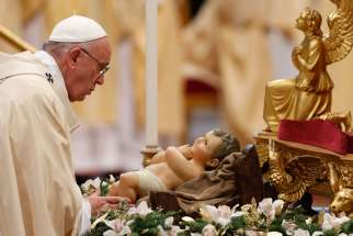 Pope Francis touches a figurine of the infant Jesus at the start of Mass marking the feast of the Epiphany in St. Peter's Basilica at the Vatican Jan. 6, 2015.