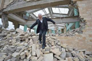 Father Emanuel Youkhana, an archimandrite of the Assyrian Church of the East, walks through the rubble of a demolished church in Mosul, Iraq, Jan. 27.