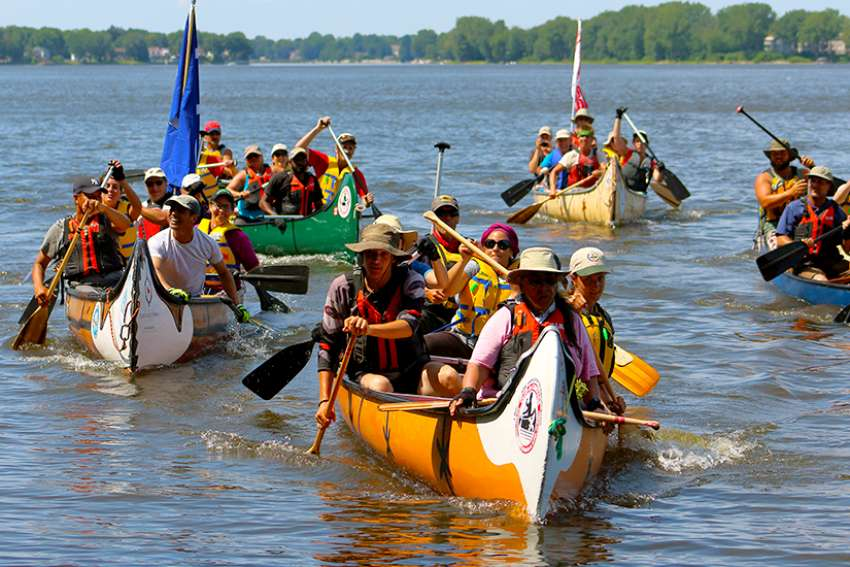Jesuit and indigenous pilgrims arriving in Kahnawake on August 15, an Indian reserve in Montreal. They reach the end of their 540-mile canoe trip, following a route used by 17th-century missionaries, in an effort to promote reconciliation.