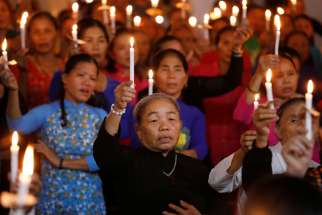 Women hold candles during a service at a church in My Khanh, Vietnam, Oct. 26, 2019, for 39 Vietnamese migrants found dead in the back of a truck at the Port of Tilbury in Essex, England. In a message to young Catholics in Vietnam, Pope Francis offered prayers for the migrants, who died while being smuggled into Great Britain in late October.