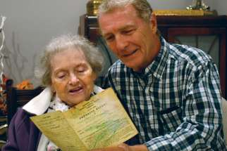 Michael McGouran looks at his Grade 3 report card from St. Monica Catholic School with his 92-year-old mother.