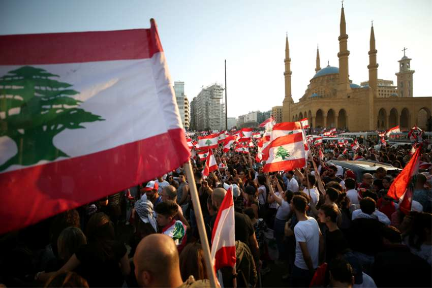 Demonstrators near Al-Amin mosque in Beirut carry national flags during an anti-government protest Oct. 20, 2019. Fueled by economic insecurity and deteriorating living conditions, protests were sparked by government plans to impose new taxes.