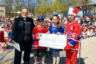 Fr. Larry Marcille, pastor of Blessed Sacrament parish in Toronto, is presented with a cheque for $3,000 by students from Blessed Sacrament School. The money is to be donated to the Family of Faith campaign.