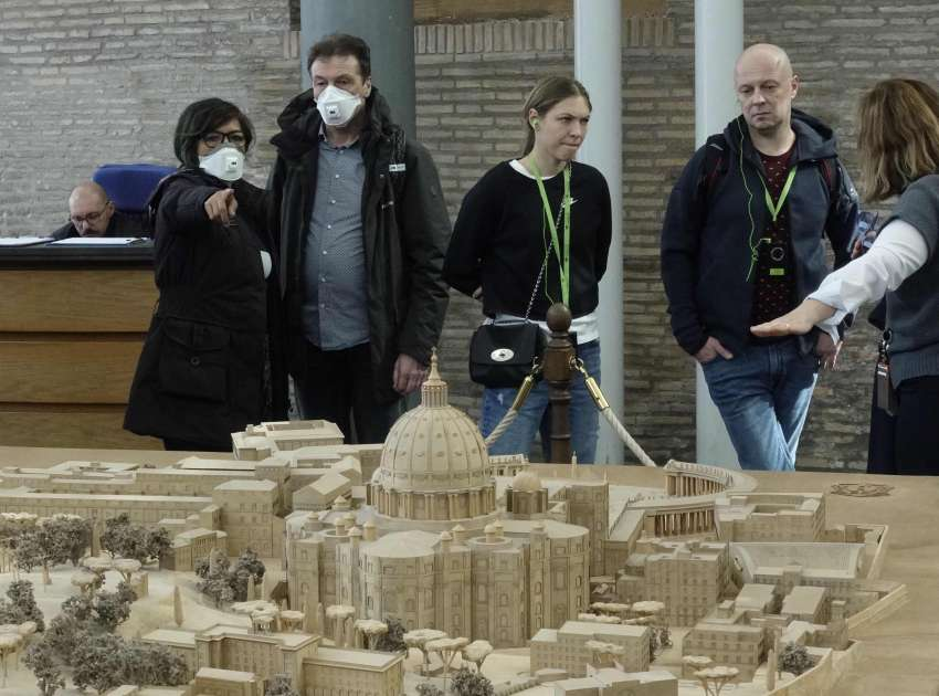 People wearing masks for protection from the coronavirus look at a model of the Vatican at the Vatican Museums. The Vatican announced March 8 that the Vatican Museums will be closed until April 3 as a precaution against spread of the coronavirus.