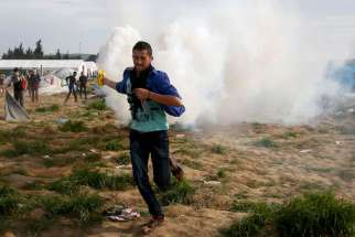 A migrant runs with a tear gas canister during clashes with Macedonian police April 10 at a makeshift camp at the Greek-Macedonian border near the village of Idomeni, Greece. Pope Francis will travel  to Lesbos, Greece, April 16.