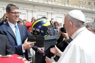 Jim Harbaugh, head football coach for the University of Michigan, presents Pope Francis with a team football helmet during the pope's general audience in St. Peter's Square at the Vatican April 26.