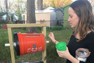 Jane Crosby stands April 17 next to a composting apparatus that she made with her brother outside her home in Springfield, Va. All her food scraps are composted so they can be used later as fertilizer, instead of decomposing and emitting methane gas in a landfill.