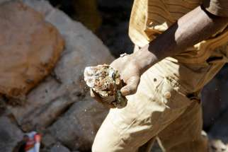 In this Aug. 16, 2016, file photo, an artisanal miner carries raw ore near Kolwezi, Congo. A representative of the Catholic bishops of Congo have called on multinational corporations working in the mineral-rich country to contribute toward local development.
