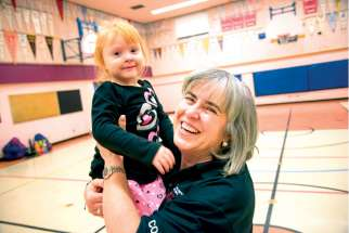 Linda Ward gives little Alessia Mussol a boost at the end of another Monday night of Special Olympics activities in the gym of St. Brigid's Catholic School.