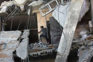 A Palestinian man examines the damage to his destroyed house following an Israeli airstrike north of Gaza City July 11. A Catholic priest in Gaza said Israeli missile attacks are wide-ranging and that there is no safe zone.
