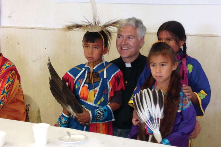 Archbishop Murray Chatlain, with First Nations children in this Register file photo, says the Catholic Church has to be there for families facing despair on a daily basis. Recently, six youth have taken their lives in his Keewatin Le-Pas diocese.