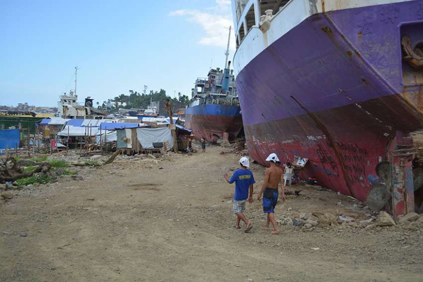 In this spring 2014 picture, residents of the Anibong shoreline shanty community coexist with cargo ships that ran aground in their neighborhood after Super Typhoon Haiyan slammed the central Philippines in November 2013.