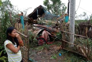 A woman in Bangui, Philippines, stands outside her house damaged by a fallen tree Oct. 20 after Typhoon Haima hit. Heavy damage was reported to homes and farmland in the northern Philippines after the strongest storm in three years struck overnight.