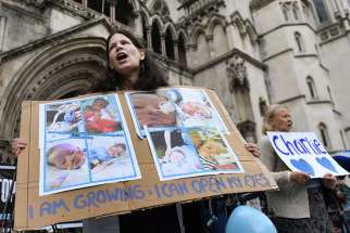 Supporters of the parents of Charlie Gard demonstrate outside England's high court in London July 13. Charlie's parents, Connie Yates and Chris Gard, petitioned the court to allow them to travel with their terminally ill child to the United States for medical treatment. The court denied their request but ruled that a U.S. doctor who specializes in the baby's condition can travel to England to examine the child.