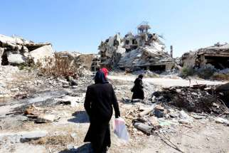 People walk amid rubble Sept. 19 in the city of Homs, Syria. Chaldean Catholic bishops at their annual synod calls for peace in the Middle East and the liberation of Islamic State controlled areas.