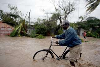 A man pushes a bicycle in floodwaters Oct. 4 in Les Cayes, Haiti, as Hurricane Matthew sweeps through the island nation.