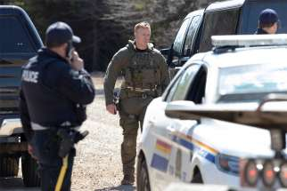 Royal Canadian Mounted Police stand along a road in Portapique, Nova Scotia, April 19, after a shooter went on 12-hour rampage that left at least 19 people dead before police killed him.
