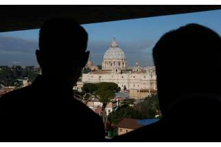 "Clergy look out on St. Peter's Basilica from an upper level of a new building. The Italian government is on ""high alert"" after a video threat made from the Islamic State group mentioned the country."