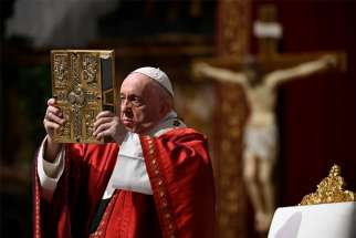 Pope Francis raises the Book of the Gospels as he celebrates Pentecost Mass in St. Peter's Basilica at the Vatican May 31, 2020.