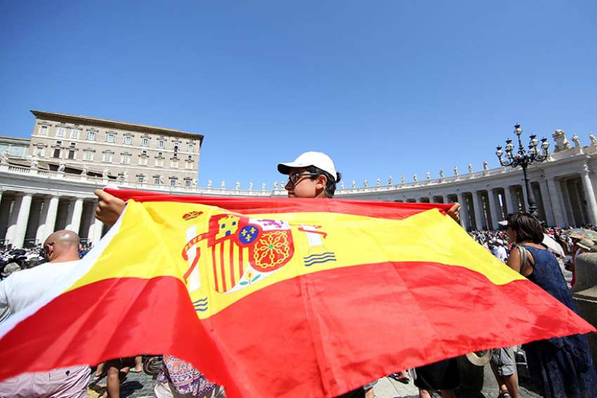 A man holds a Spanish flag as Pope Francis leads the Angelus Aug. 27 in St. Peter's Square at the Vatican.