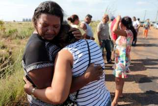 Relatives of prisoners reacts as they wait for news at a checkpoint close to the a prison where at least 33 people were killed during a Jan. 6 riot in Roraima, Brazil.