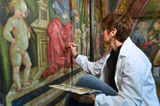 Art restorer Stefania Culesanti puts finishing touches on a red robe in the music section of the Hall of the Liberal Arts in the Borgia Apartments in the Vatican Museums on Dec. 12, 2016.