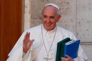 Pope Francis waves as he leaves a session of the Synod of Bishops on the family at the Vatican Oct. 24.