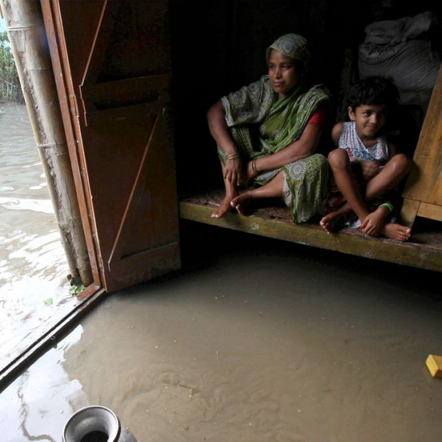 Residents sit inside their flooded house in the Indian state of Assam. Incessant heavy rains in northeast India have caused massive flooding and landslides, leaving at least 126 people dead and affecting 3 million others.