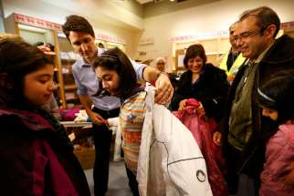 Canadian Prime Minister Justin Trudeau helps a young Syrian refugee try on a winter coat after she and others arrived Dec. 10 from Beirut to Toronto.