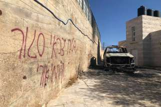 "Graffiti is seen in Hebrew on a wall next to a car was burned in the Palestinian town of Taybeh, east of Ramallah, West Bank. The Assembly of Catholic Ordinaries of the Holy Land condemned vandalism attacks in two Arab villages and called on Israeli authorities to ""investigate seriously"" what they termed hate crimes."