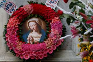 An image of Mary is the centerpiece of a wreath at the base of a Marian statue overlooking the Spanish Steps in Rome Dec. 8, the feast of the Immaculate Conception.
