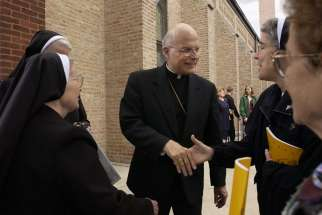 Cardinal Francis George greets people in 2003 following Mass in celebration of the 100th Anniversary of St. George's Church in Chicago. Cardinal George, 78, died April 17 after a long battle with cancer.